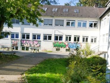 Schulhof RaS: Asphaltdecke versiegelt belastete Schotterschicht